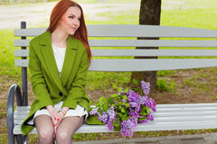 Beautiful sexy girl with long hair in ryzhymi green coat sitting on a park bench with a bouquet of lilac in the hands of Stock Photos