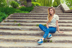 Beautiful sexy girl with long hair sitting on the stairs sad in jeans and shirt Stock Photos