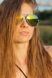 Beautiful sexy girl with long hair with tanned skin wearing sunglasses on the beach of Sunny warm day Stock Photography