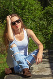 Beautiful sexy girl with long hair in a white t-shirt and jeans sitting in the woods on a Sunny day Royalty Free Stock Photography