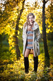 Beautiful sexy girl with long leather boots and short dress posing in park in autumn day. Beautiful elegant woman in autumn park .Young pretty woman with long Royalty Free Stock Photo