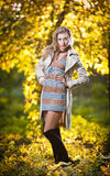 Beautiful sexy girl with long leather boots and short dress posing in park in autumn day. Beautiful elegant woman in autumn park .Young pretty woman with long Royalty Free Stock Photography