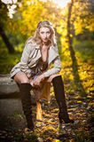 Beautiful sexy girl with long leather boots and short dress posing in park in autumn day. Beautiful elegant woman in autumn park .Young pretty woman with long Stock Photography