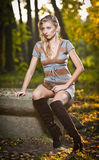 Beautiful sexy girl with long leather boots and short dress posing in park in autumn day. Royalty Free Stock Images