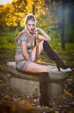 Beautiful sexy girl with long leather boots and short dress posing in park in autumn day. Beautiful elegant woman in autumn park .Young pretty woman with long Royalty Free Stock Photos