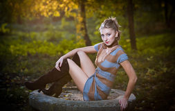 Beautiful sexy girl with long leather boots and short dress posing in park in autumn day Stock Photos