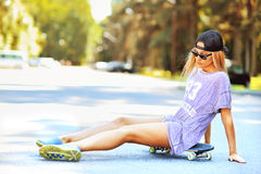 Beautiful sexy girl with long legs in jeans short sits on skateb Royalty Free Stock Images
