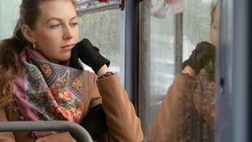 Beautiful sexy girl looking sad at the window of a streetcar. stock footage