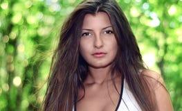 Beautiful sexy girl looking at you against spring green bokeh ba Royalty Free Stock Photos