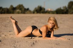 Beautiful sexy girl lying on sand in black swimsuit Royalty Free Stock Images