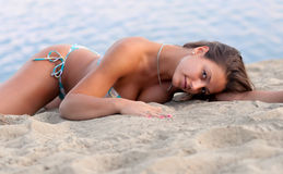 Beautiful sexy girl lying on the sandy beach Royalty Free Stock Photos