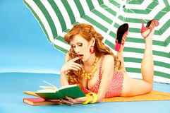 Beautiful sexy girl pin up on beach under sun. Beautiful sexy girl pin up in a pink bikini reads book on the beach under sun umbrella Stock Photography