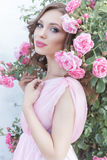 Beautiful sexy girl in a pink dress standing in the garden roses in a sunny bright summer day with a gentle make-up and bright puf Stock Image