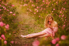 Beautiful girl in a pink dress standing in the garden roses royalty free stock photos