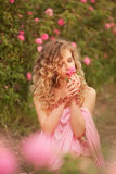 Beautiful girl in a pink dress standing in the garden roses stock photos