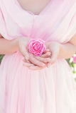 Beautiful sexy girl in a pink dress, standing in the garden on a sunny bright summer day holds a rose in hands Royalty Free Stock Photo