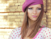 Beautiful girl in a pink hat with beautiful makeup in the white jacket in pink polka dot stands on a Sunny autumn day Stock Photos