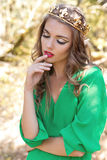 Beautiful sexy girl Queen with bright makeup in a long dress with a crown on his head busick walks in the forest in bright Sunny s Royalty Free Stock Photography