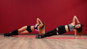 Beautiful sexy girl on a red background wall doing fitness exercises on a special shoes kango jump.  stock footage