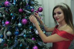 Beautiful girl in red dress decorating a Christmas tree with balloons looks into the camera. Design on the theme of women in stock photography