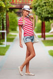 Beautiful sexy girl in shorts and striped t-shirt, in hat, outdoors. Tanned girl in summer Stock Photography