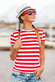 Beautiful sexy girl in shorts and striped t-shirt, in sunglasses, in hat, outdoors. Tanned woman in summer Royalty Free Stock Image