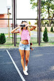 Beautiful sexy girl in shorts and sunglasses posing with old cam Stock Images