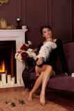 Beautiful sexy girl sitting near the fireplace in a romantic with candles and holding pen Royalty Free Stock Photography