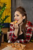 Beautiful and girl sitting at a table with a pizza in a cafe. stock photography