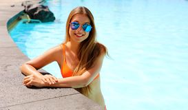 Beautiful sexy girl with sunglasses and bikini relaxing in swimming pool in resort spa hotel on her travel holidays in Tenerife. Copy space stock photo