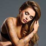 Beautiful sexy girl with a tattoo on the body. Portrait of young adult attractive woman with brown hair Stock Image