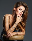 Beautiful sexy girl with a tattoo on the body. Portrait of young adult attractive woman with brown hair Royalty Free Stock Photo