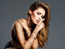 Beautiful sexy girl with a tattoo on the body. Portrait of young adult attractive woman with brown hair Royalty Free Stock Photos