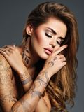 Beautiful sexy girl with a tattoo on the body. Portrait of young adult attractive woman with brown hair Stock Photography