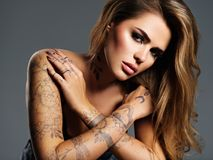 Beautiful sexy girl with a tattoo on the body. Portrait of young adult attractive woman with brown hair Royalty Free Stock Image