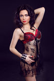 Beautiful and girl wearing red lingerie over dark. Attracti Royalty Free Stock Photo