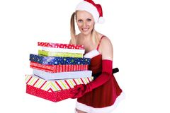 Beautiful girl wearing Santa Claus clothes, arms full of gifts. stock photo