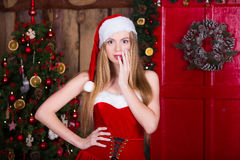 Beautiful sexy girl wearing santa claus clothes in new year interior. Young female posing in christmas dress, hat and Royalty Free Stock Images