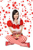 Beautiful sexy girl wearing santa claus clothes, red stars backg Stock Photos