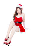 Beautiful sexy girl wearing santa claus clothes and sitting isol Stock Photo