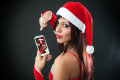 Beautiful sexy girl wearing santa claus clothes with smartphone Royalty Free Stock Photography
