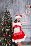 Beautiful sexy girl wearing santa claus clothes . Smiling woman with big and small gift. Women on dress and santa`s hat. Royalty Free Stock Photo