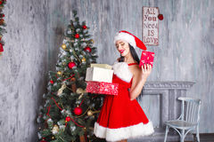 Beautiful sexy girl wearing santa claus clothes . Smiling woman with big and small gift. Women on dress and santa`s hat. Royalty Free Stock Photography