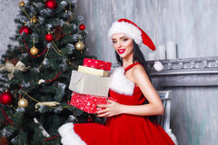 Beautiful sexy girl wearing santa claus clothes . Smiling woman with big and small gift. Women on dress and santa`s hat. Royalty Free Stock Image