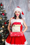 Beautiful sexy girl wearing santa claus clothes . Smiling woman with big and small gift. Women on dress and santa`s hat. Stock Photos