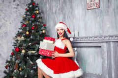 Beautiful sexy girl wearing santa claus clothes . Smiling woman with big and small gift. Women on dress and santa`s hat. Stock Images