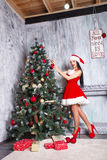 Beautiful sexy girl wearing santa claus clothes . Young woman decorating Christmas tree with red balls at home Royalty Free Stock Photography