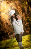 Beautiful sexy girl in white posing in park in autumn day. Beautiful elegant woman with white cap in autumn park Stock Images