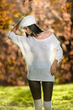 Beautiful sexy girl in white posing in park in autumn day. Beautiful elegant woman with white cap in autumnal park Royalty Free Stock Images
