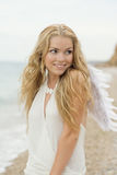 The beautiful sexy girl with wings on seacoast. The beautiful blonde with angelic wings on the sea Royalty Free Stock Photos